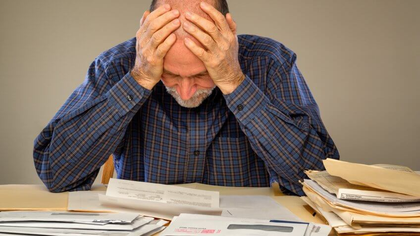 A senior adult man sitting at a table or desk stacked with papers and envelopes looking down with his hands on his head.