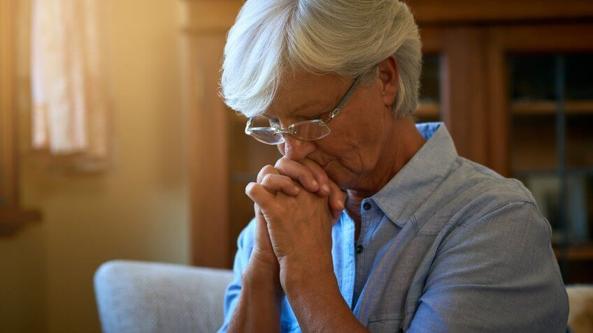 senior woman looking worried with her hands clasped together at home