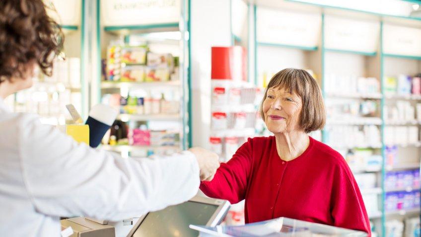 Senior female customer standing at chemist counter as pharmacist hands her medication order.