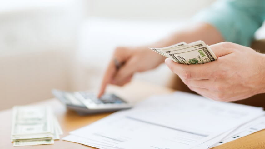 man with calculator counting money and making notes at home