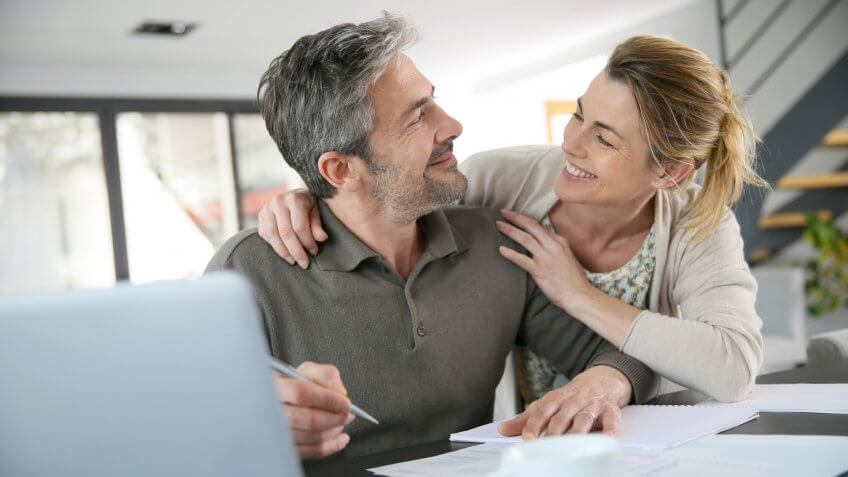 Couple calculating financial savings on internet.