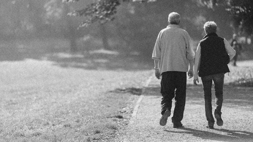happy retired couple on a walk together in the park