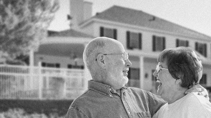laughing older couple in front of a house