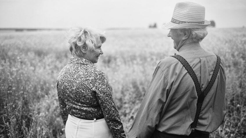 retired couple on a walk in a field