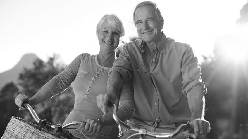 happy retired couple biking together