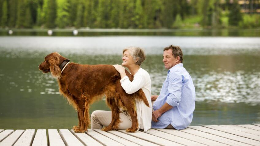 Senior couple with dog sitting on pier above the mountain lake with mountains in background.