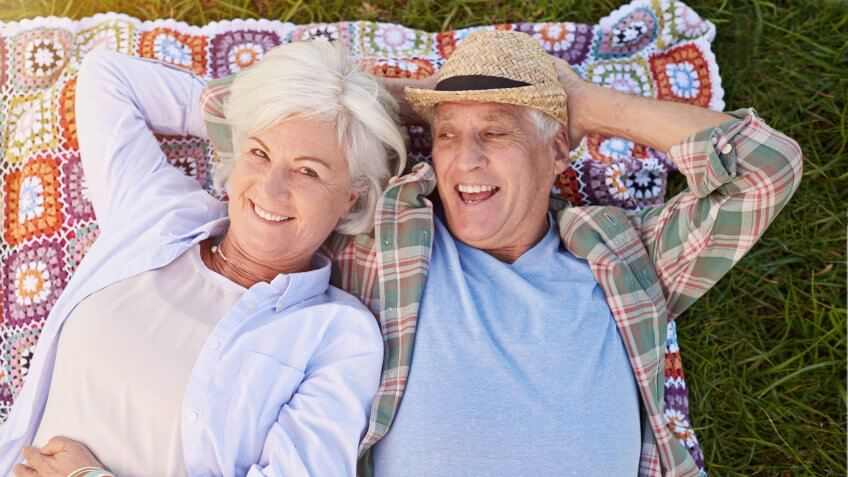 Portrait of a happy senior couple relaxing together on the lawnhttp://195.