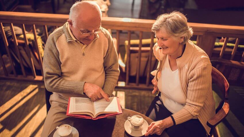 High angle view of a senior man reading a book to his wife in a cafe who is enjoying listening to him.