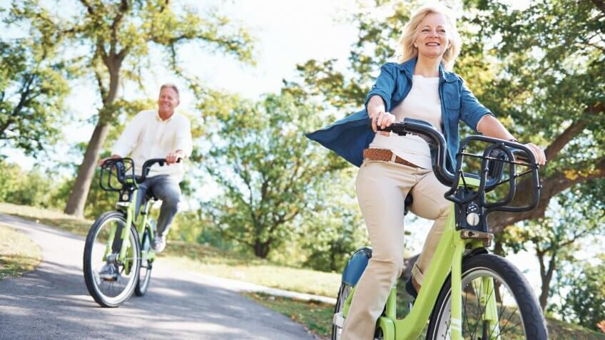 Portrait of a happy senior couple enjoying a bicycle ride in the park together.