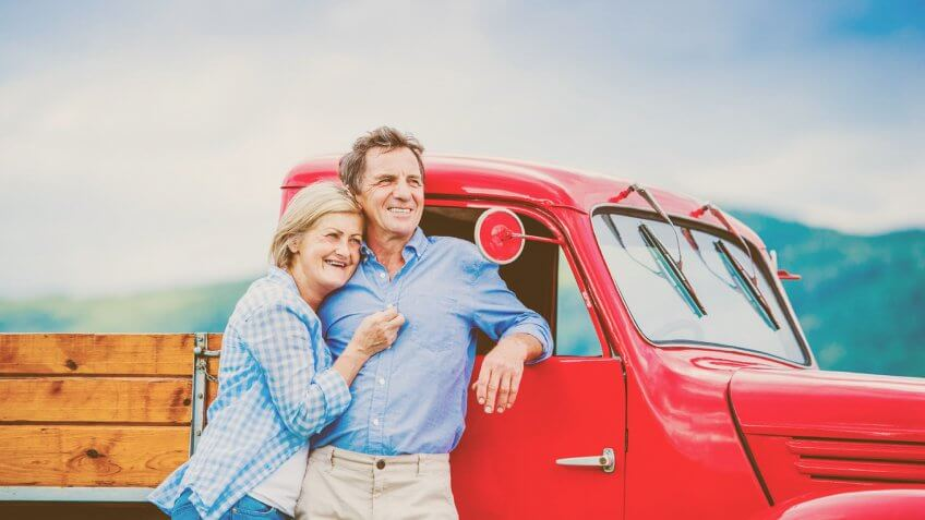 older couple standing beside a vintage red truck