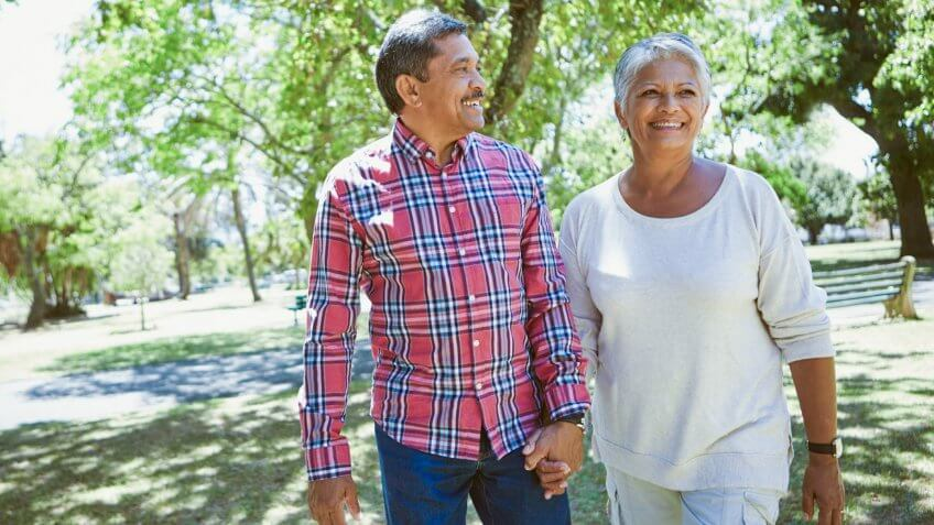 retired couple walking in the shade in a park