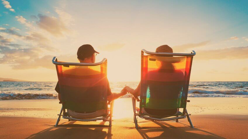 retired couple relaxing in chairs on the beach
