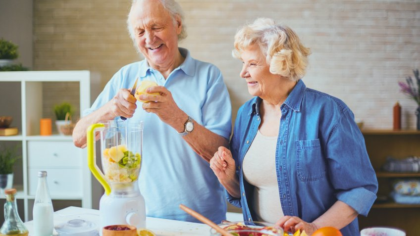 elderly couple making food with a blender