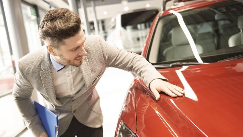 man looking at new car