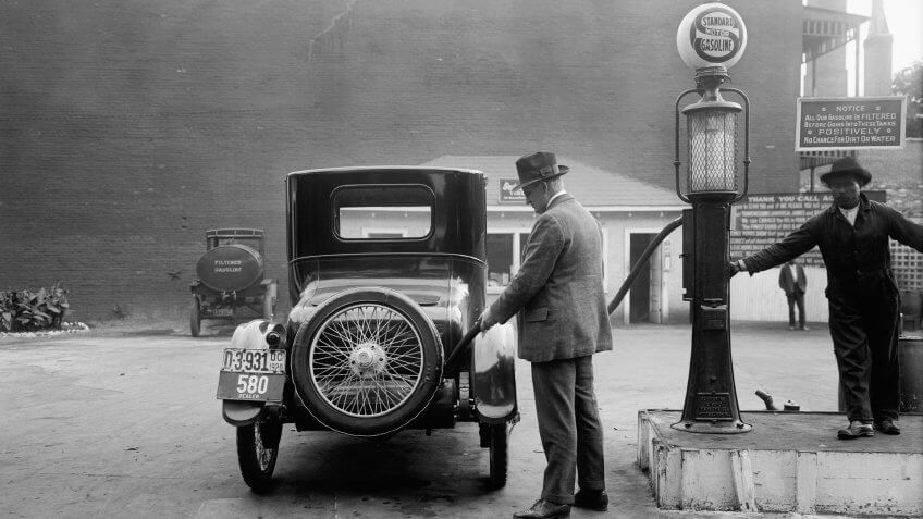 Man fueling his car at a self-service Standard Motor gas station, What $100 Was Worth in the Decade You Were Born