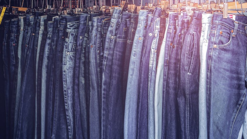 A rack of a variety of blue denim jeans in various shades of blu, What $100 Was Worth in the Decade You Were Born