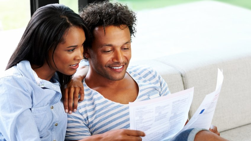 Young couple sitting on sofa reading a financial bill at home.