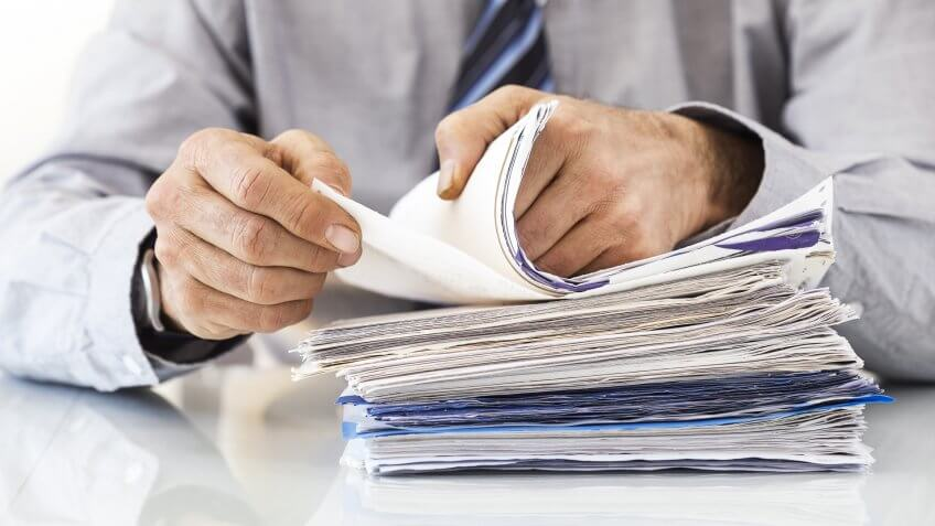 man sorting stack of papers