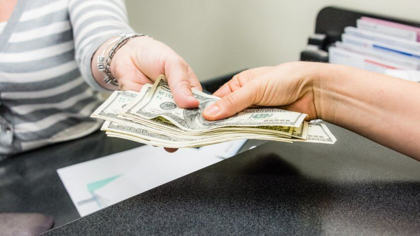 women hands getting cash in a bank teller.