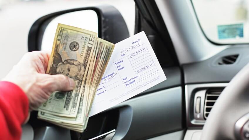 A man in his car is holding five hundred dollars in US twenties and a bank deposit slip while waiting in line for a bank drive through teller window.