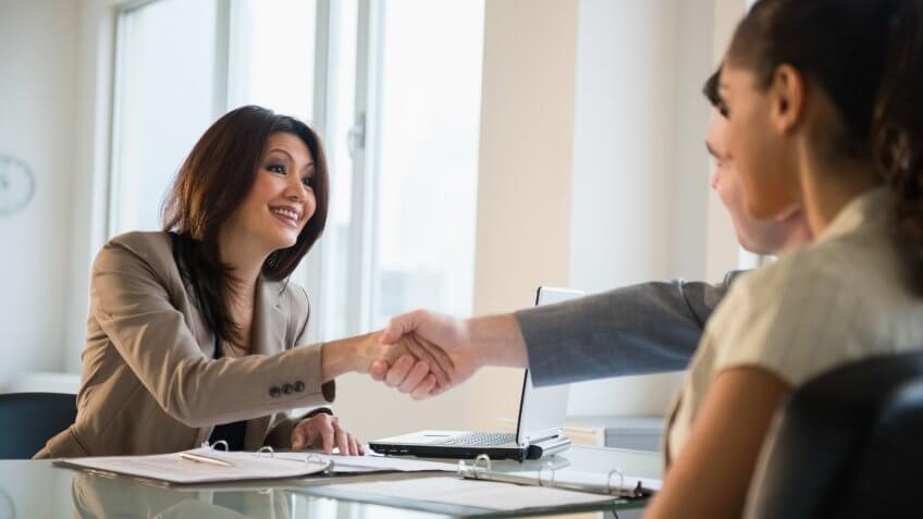 Businesswoman shaking hands with clients at desk.