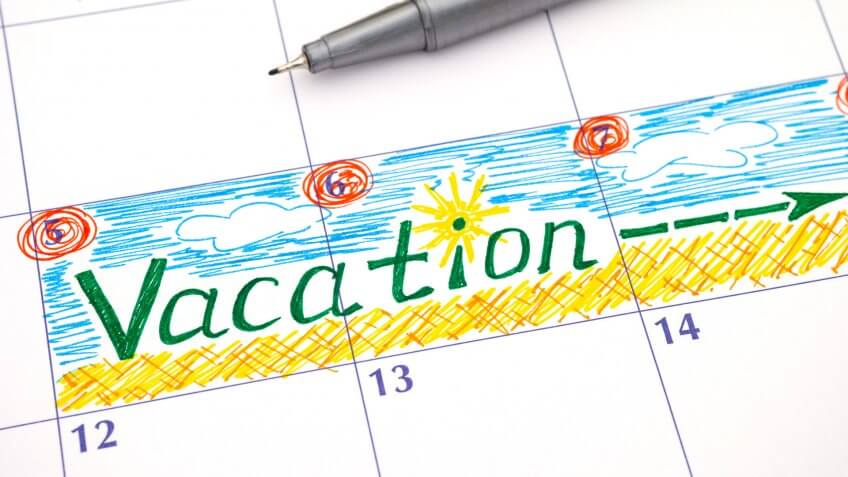 Reminder Vacation in calendar with pen.