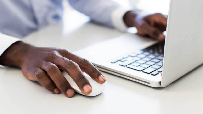 Close up of an African businessman sitting at his desk working on a laptop using a mouse.