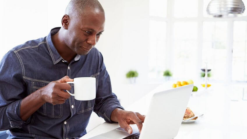 man drinking coffee on laptop