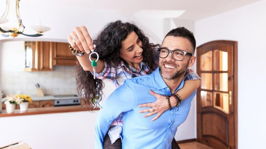 Young couple moving in new apartment, holdinh keys, in piggyback ride.