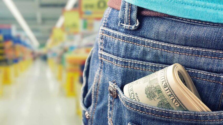 10 Items You Should Never Get at the Dollar Store, Closeup of money in the pocket against grocery market