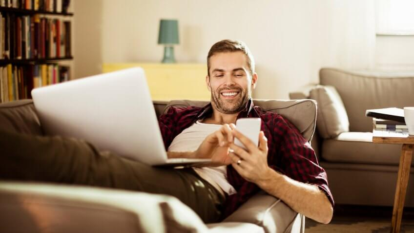 Photo of a handsome mature man lying on sofa and texting on his smart phone.