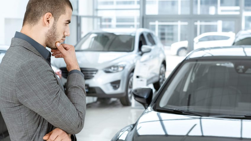 young man looking at a new car in thought