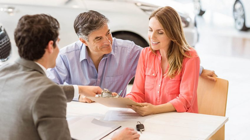 couple looking over documentation while speaking with a salesperson
