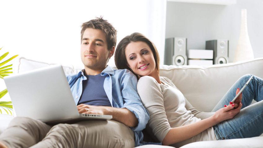 couple looking at a laptop while sitting on the couch