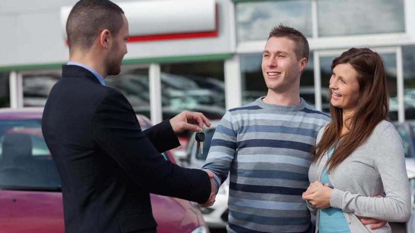 smiling couple receiving keys to their new car