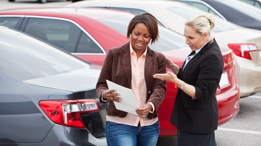 Woman shopping for a new car, with a saleswoman.