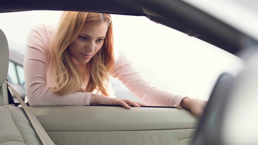 woman inspecting a car's interior