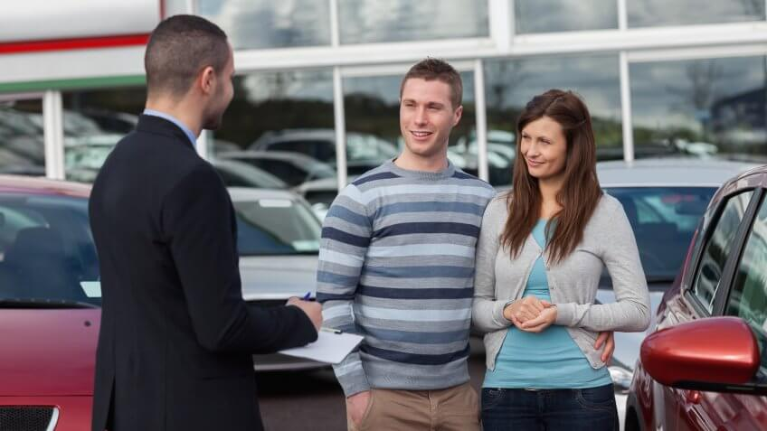 Salesman talking to a couple in a dealership.