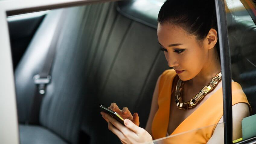 Young businesswoman in Hong Kong taxi, using smartphone.