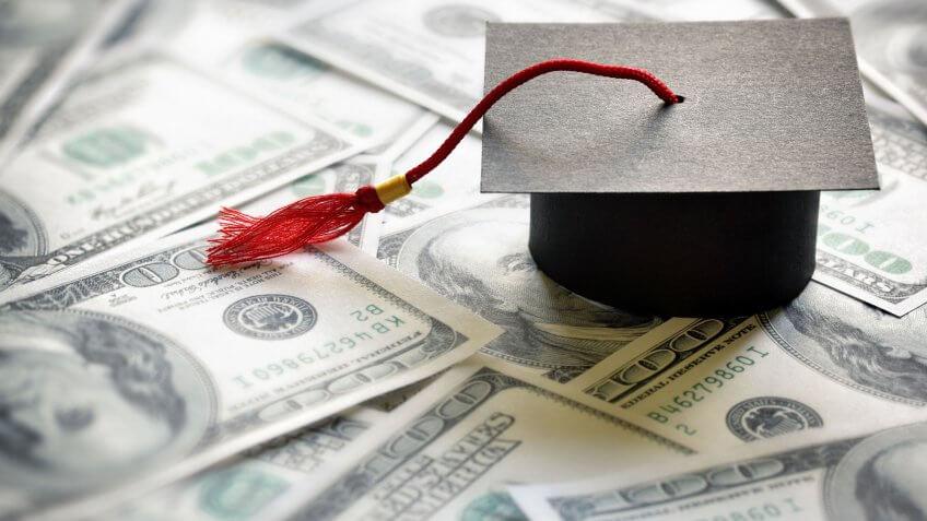 mini graduation cap on 100 dollar bills