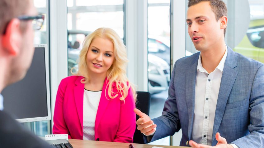 couple negotiating the price of a car with a salesperson