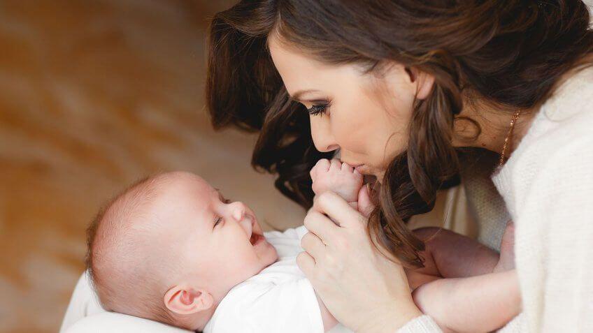 mom kissing infant hands