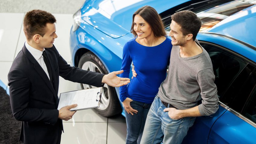 car salesman speaking with a young couple about a new car