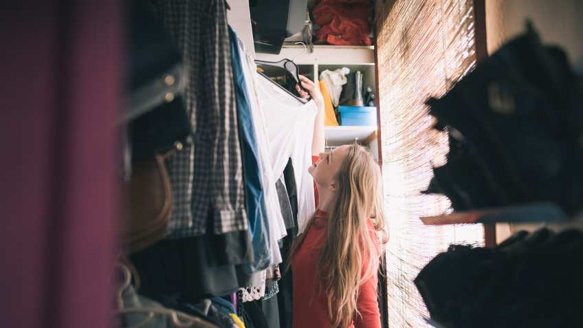 girl searching for clothes in her messy closet
