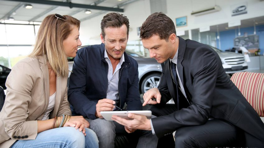 car salesman showing a couple information on a tablet