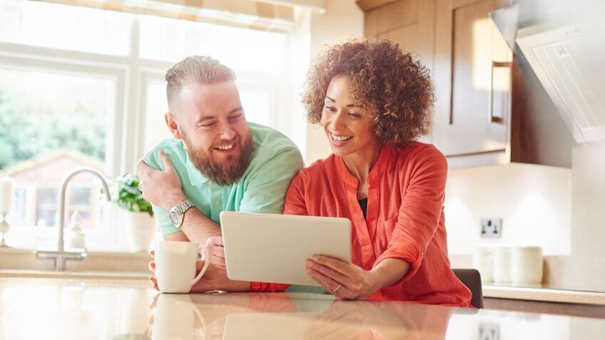 a mid adult man and woman sit in their kitchen and look on their digital tablet internet shopping or checking their online account .