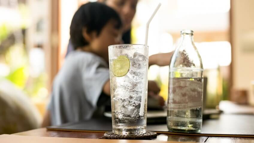 Healthy nutrition of drinking water with lemon and people in blur background.