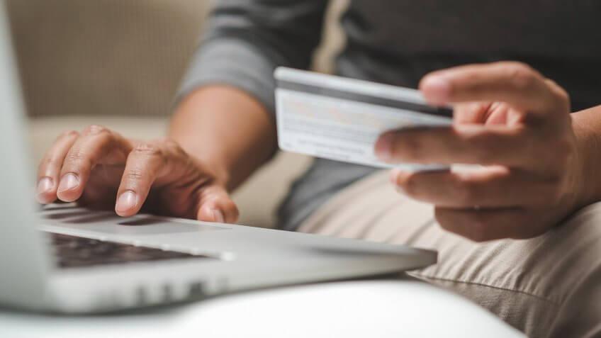 Internet shopper entering credit card information using laptop keyboard.