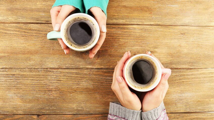 Female hands holding cups of coffee on rustic wooden table background.