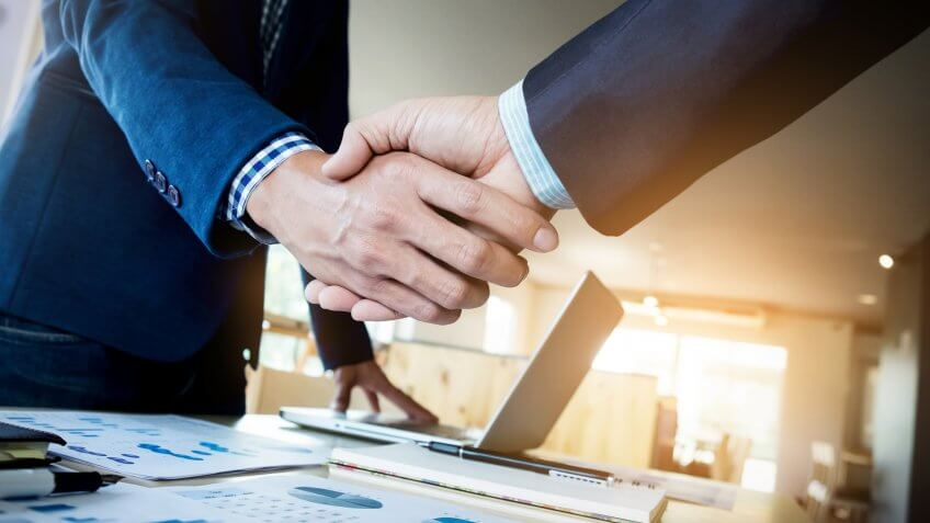 Biggest Money Scams of All Time, Two confident business man shaking hands during a meeting in the, dealing, greeting and partner concept., success